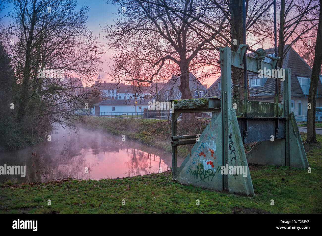 Germany, Grevenbroich, Erft river bend at weir of former 'Eisener Muehle' in the evening - Stock Image