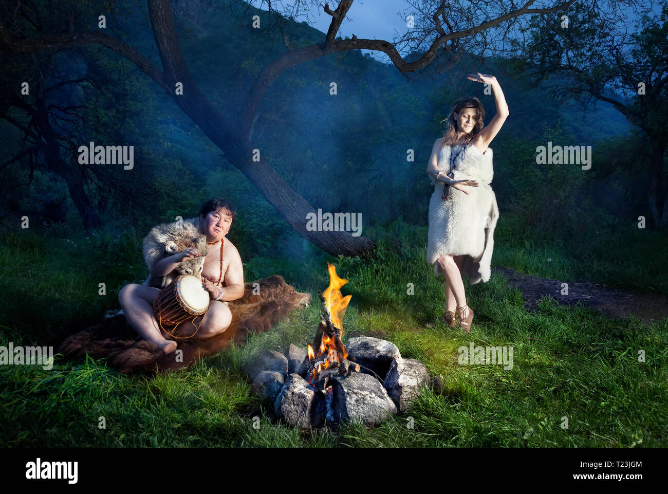 Caveman dressed in wolf skin playing drum and cave woman dancing near bonfire in the forest - Stock Image