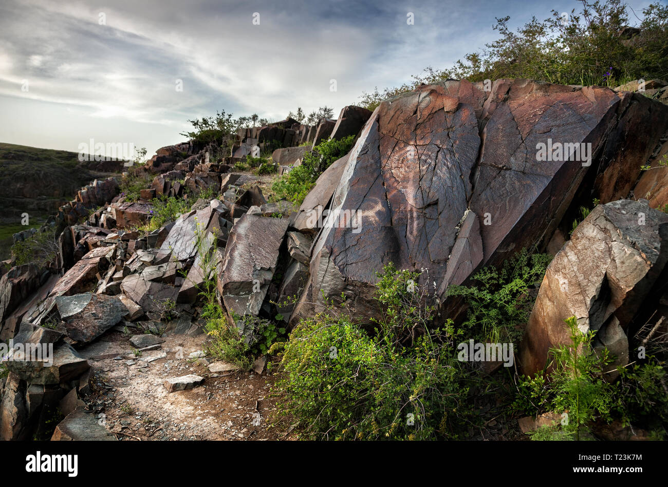 Ancient petroglyph of sun man on the stone in open air museum Tanbaly at sunset sky background - Stock Image