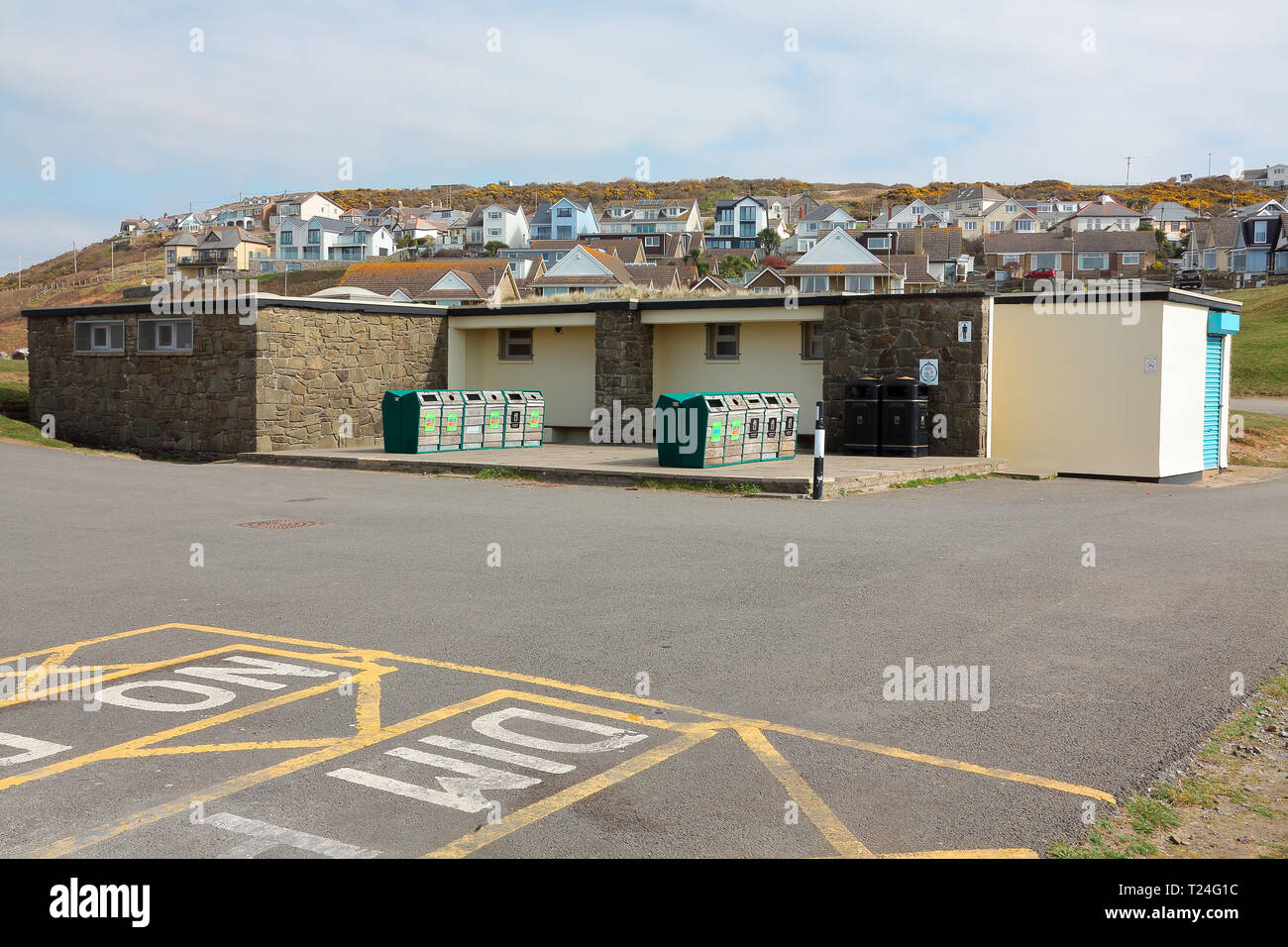 The toilet block in Ogmore by sea beach car park with shuttered doors and a variety of waste bins outside as the beach area is very busy in summer. - Stock Image