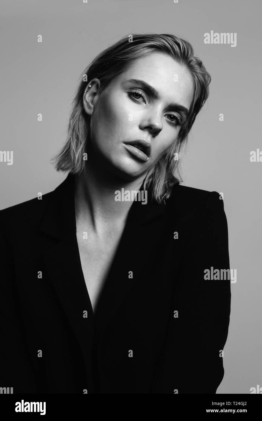Portrait of blond young woman wearing black blazer - Stock Image