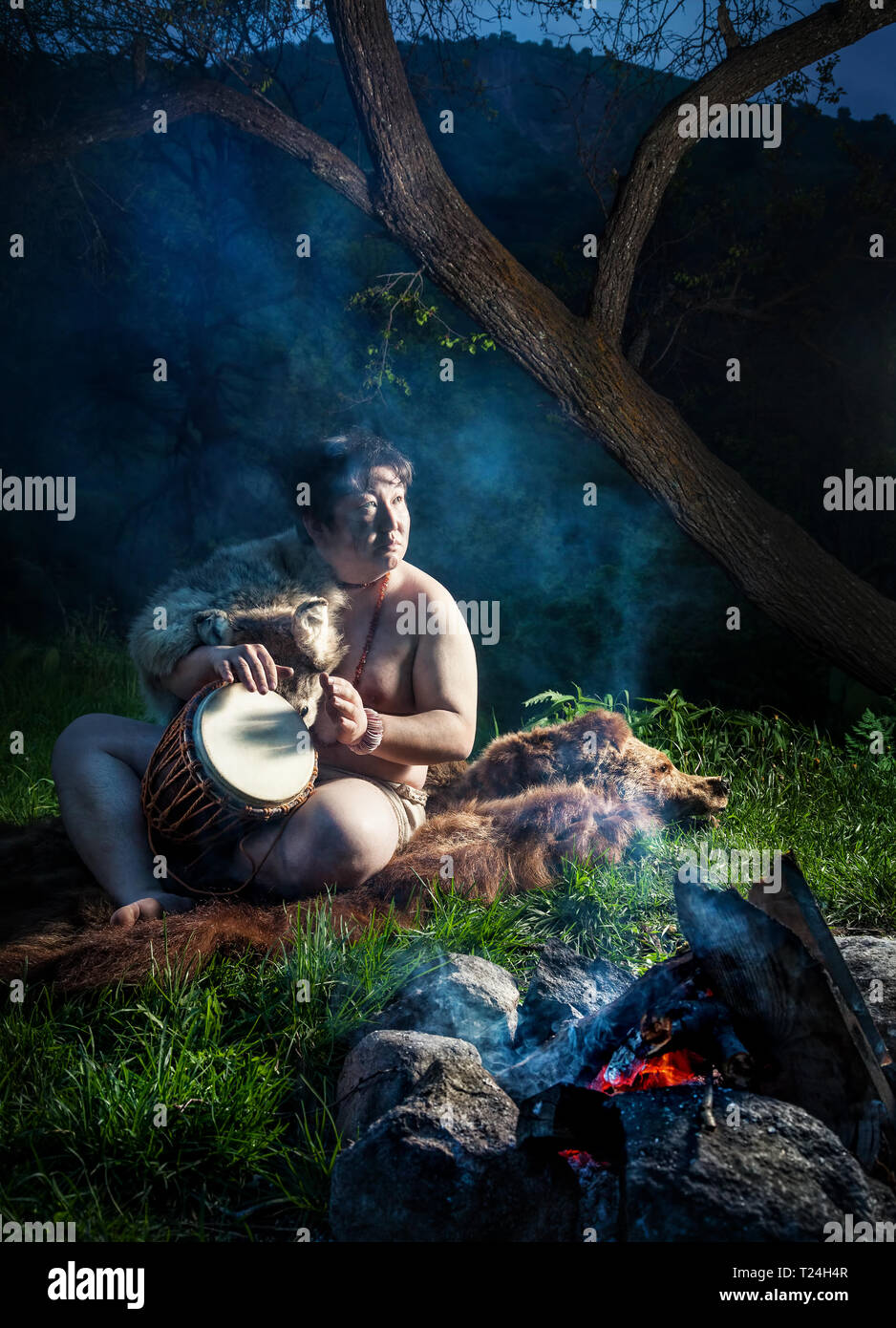 Caveman dressed in wolf skin playing drum near bonfire in the forest Stock Photo