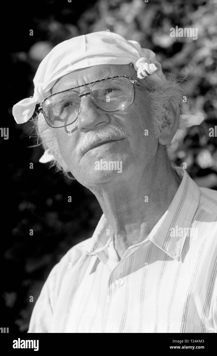 Elderly Man Wearing a Handkerchief Tied in Four Corners on his head as a Sun Hat - Stock Image