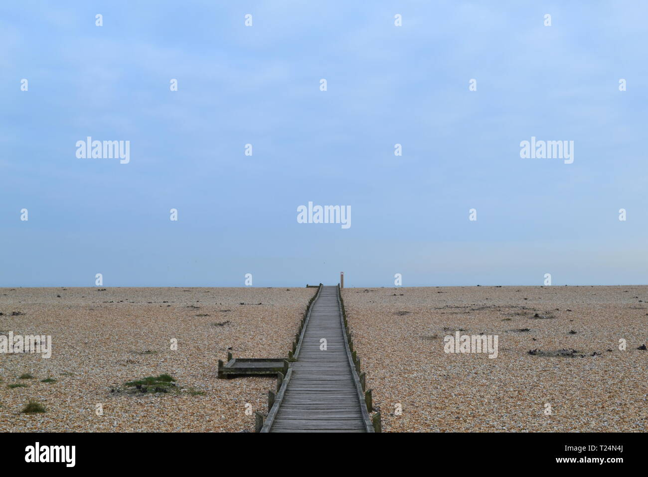 The boardwalk leading to the sea across the shingle at Dungeness, Kent, UK, a nature reserve. At the other end of the boardwalk is the Britannia Inn - Stock Image