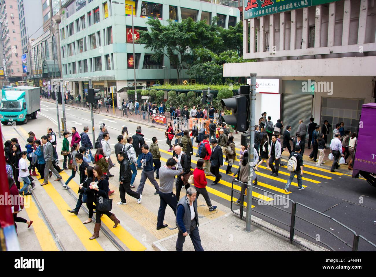 Hong Kong, December 2013: Busy pedestrian crossing at Hong Kong, viewed from the tram. Stock Photo