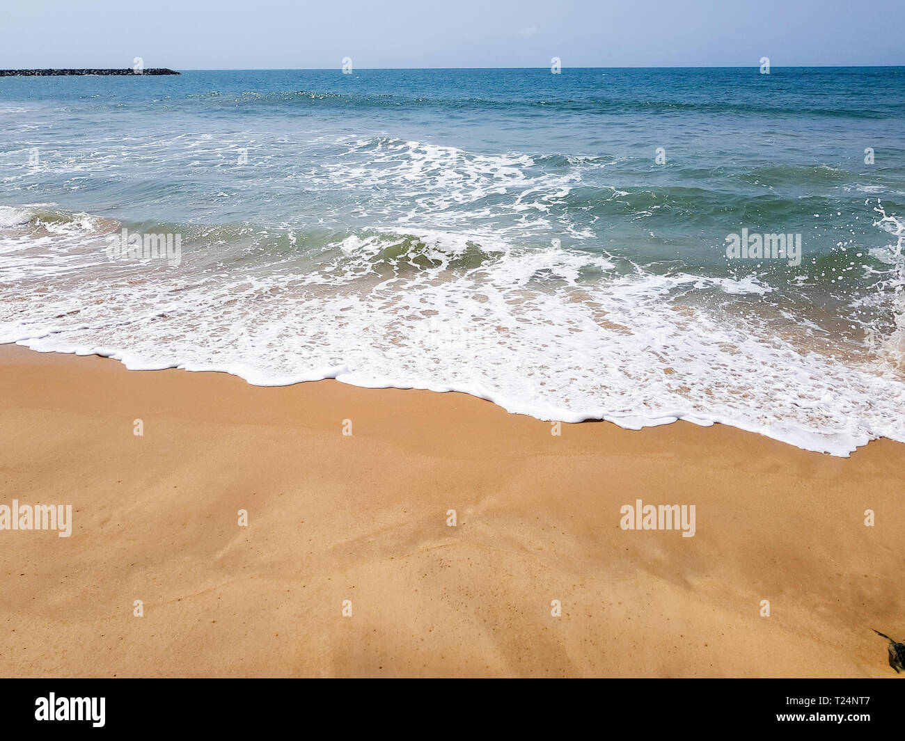 Waves with white sea foam on a sandy beach at low tide in Lagos, Nigeria. Beautiful waterfront view of the Atlantic ocean with copy space. - Stock Image