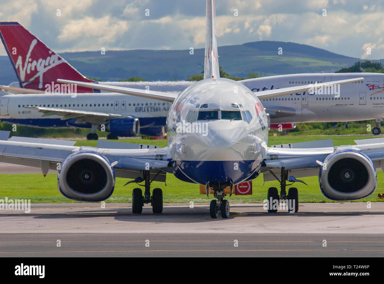 A British Airways Boeing 737 taxis at Manchester Airport. Busy airport scen with three planes in one picture. - Stock Image