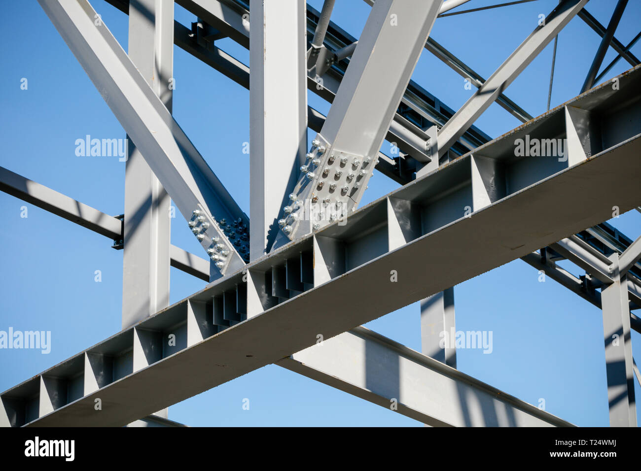Steel frame of new building in construction - girder joint detail, set against bright blue sky - Stock Image