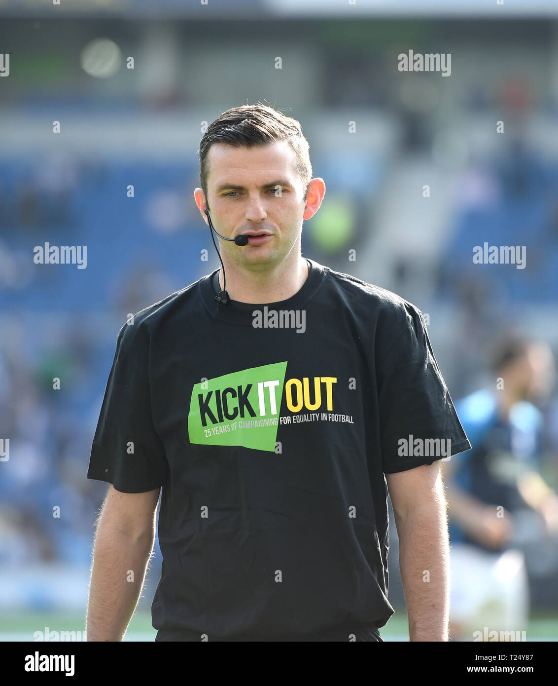 Referee Michael Oliver wearing a Kick it Out shirt before the Premier League match between Brighton & Hove Albion and Southampton at The American Express Community Stadium . 30 March 2019 Editorial use only. No merchandising. For Football images FA and Premier League restrictions apply inc. no internet/mobile usage without FAPL license - for details contact Football Dataco - Stock Image