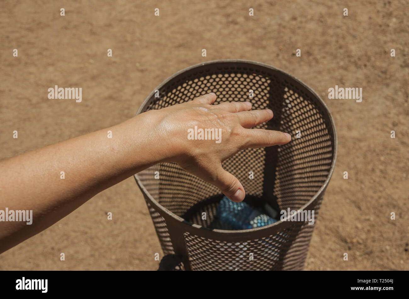 Hand of woman throwing a plastic bottle inside a trash can on a park at Merida. The city preserves many buildings of ancient Rome in Spain. - Stock Image