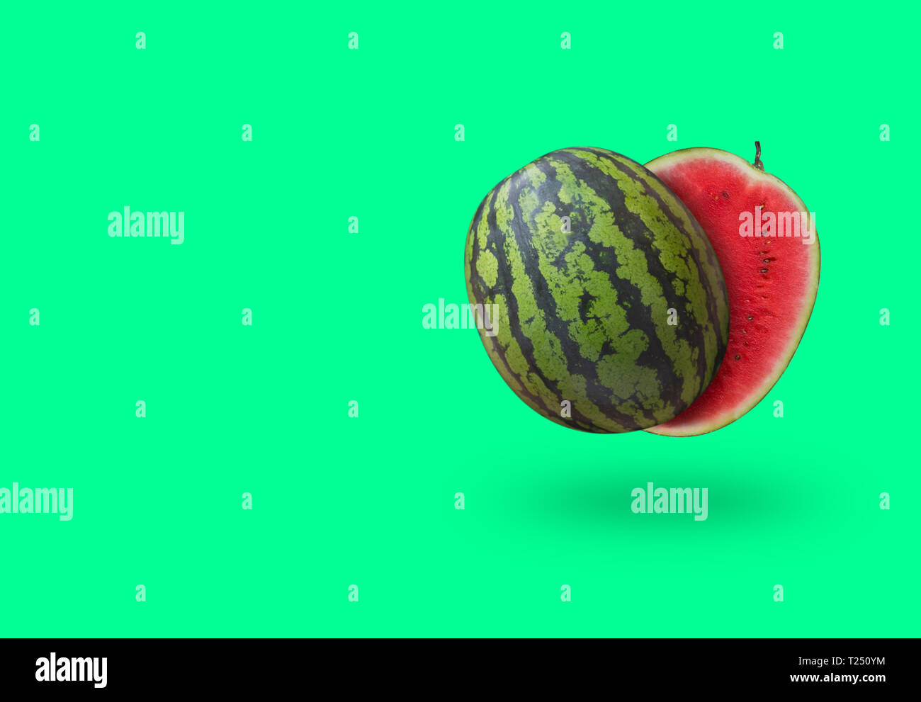 Cutted watermelon isolated on green pastel background with a shadow and copy space. Horizontal orientation - Stock Image
