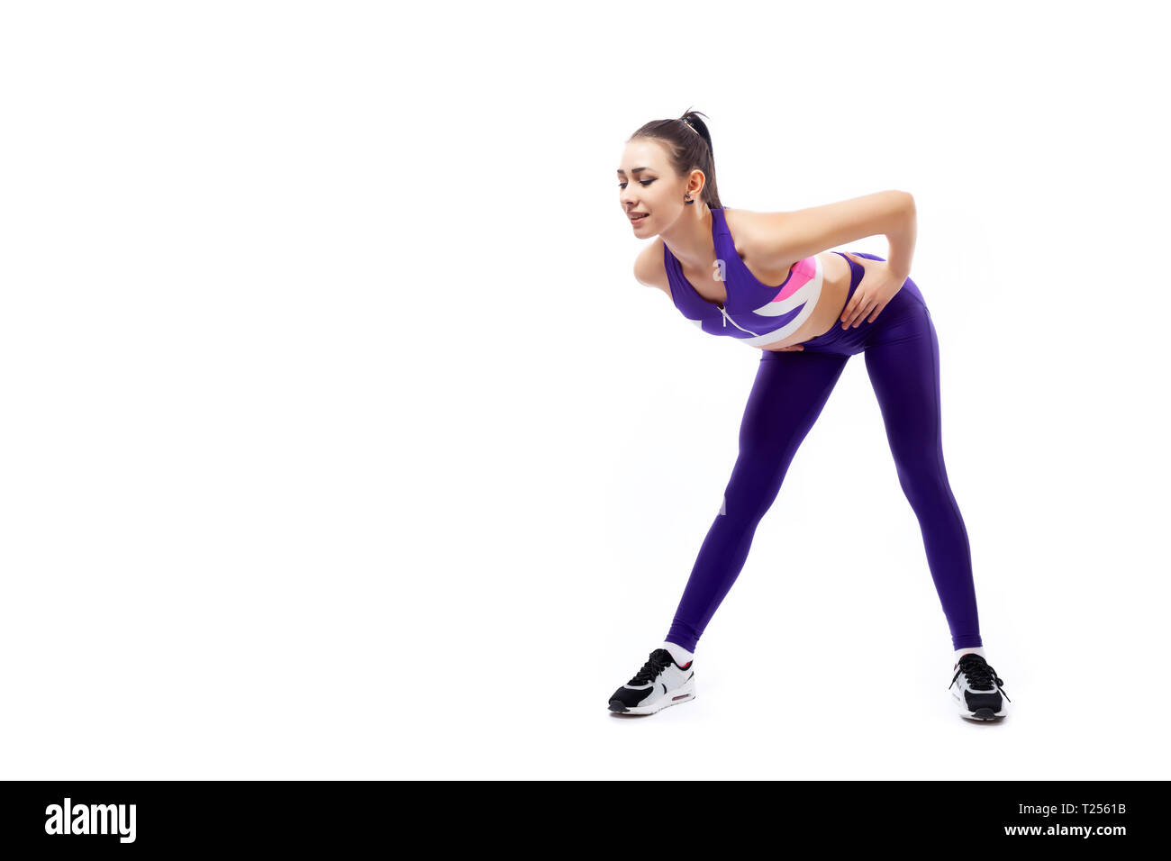 A dark-haired woman coach in a sporty purple  short top and gym leggings shows the correct technique of tilting forward for inflating the buttocks on  - Stock Image