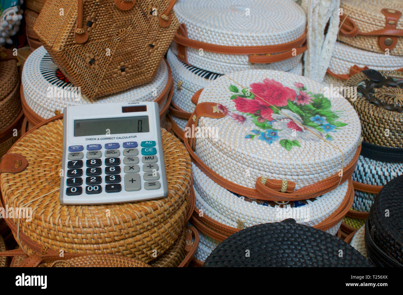 Close up picture of an calculator on a group of brown and white rattan bags displayed at the Ubud Art Market in Bali ,Indonesia - Stock Image