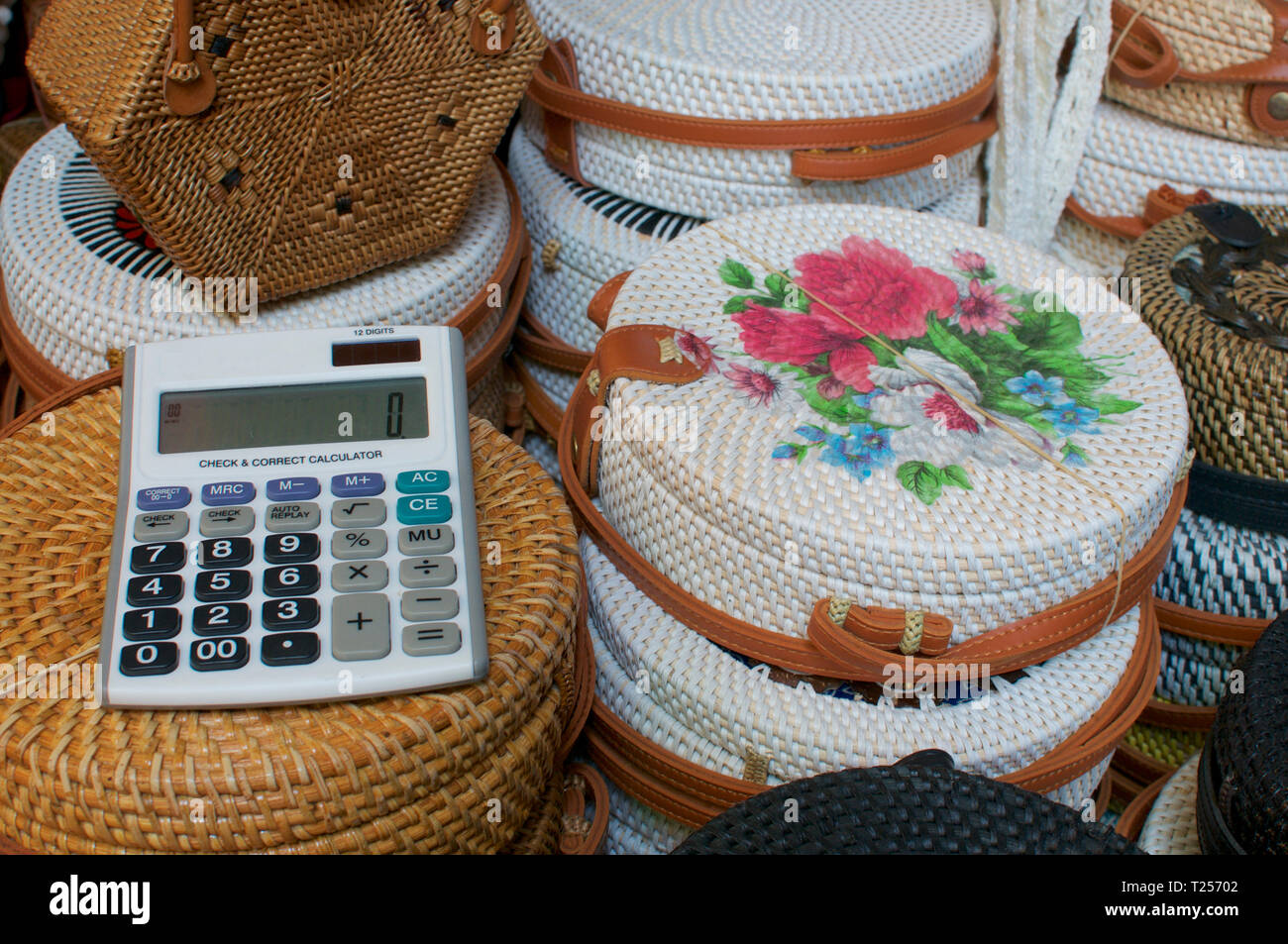 Close up picture of an calculator on a group of brown and white rattan bags captured on at the Ubud Art Market in Bali ,Indonesia - Stock Image