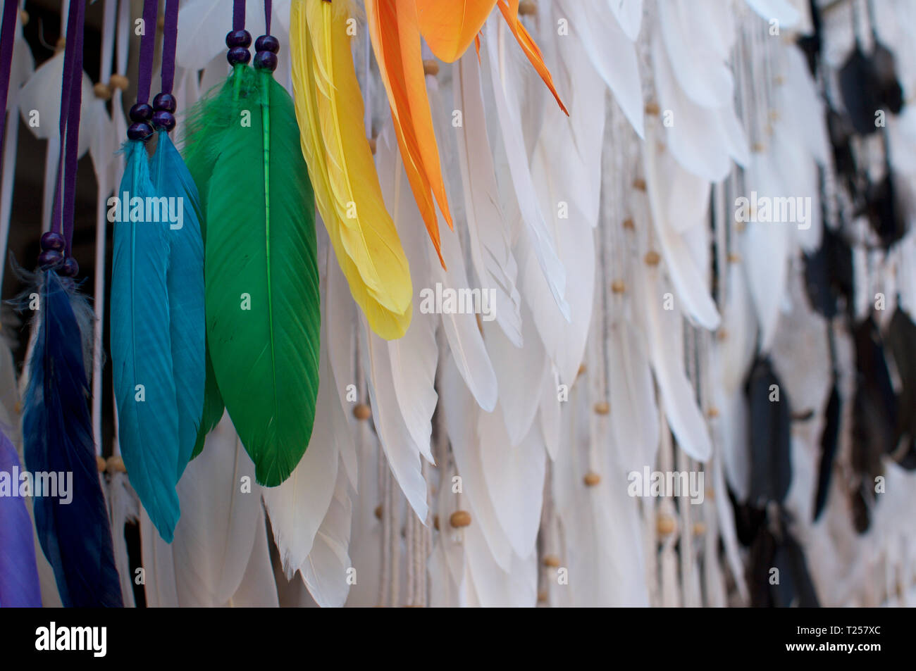 Beautiful close of colored and white feathers of a dreamcatcher hanging at the Ubud Art Market in Bali, Indonesia - Stock Image