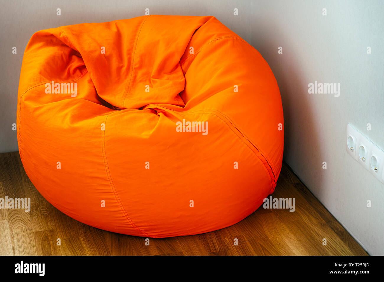 Orange beanbag in room corner - Stock Image