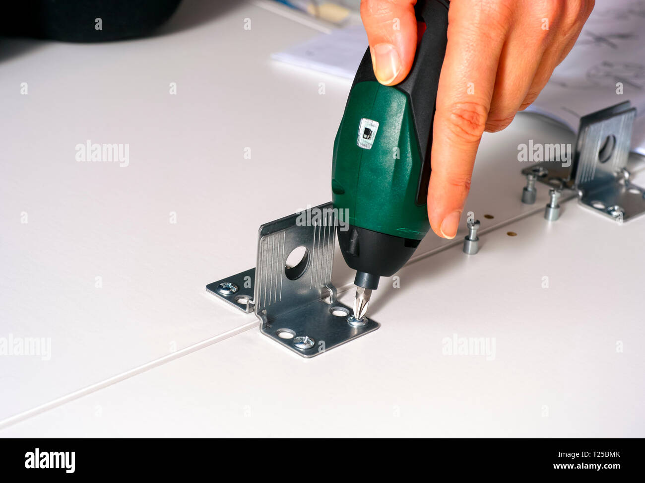 Woman hand with screw drill twisting the screw into the furniture. Close-up. - Stock Image