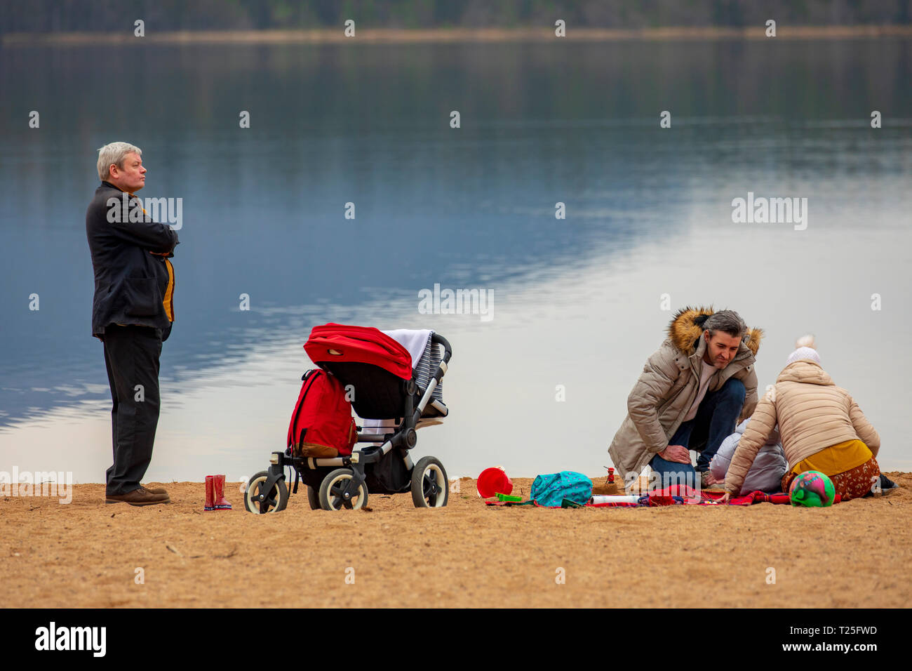 A family enjoying the spring like February weather on the shore of Loch Morlich near Aviemore in the Glenmore Forest Park, Scotland - Stock Image