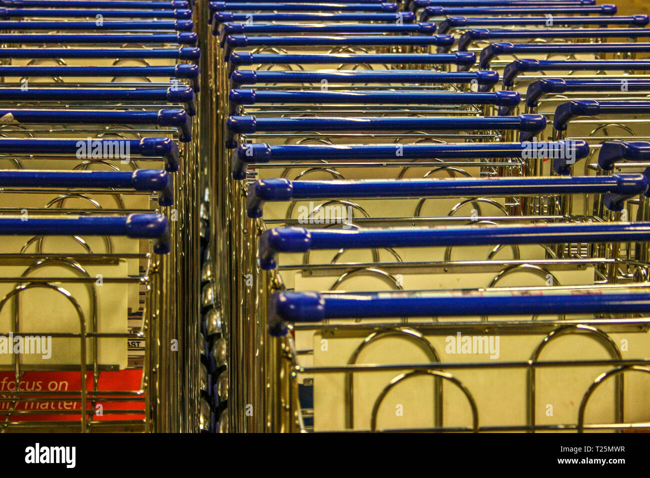 line of shopping trolleys with blue handrails in a shopping mall - structure - Stock Image