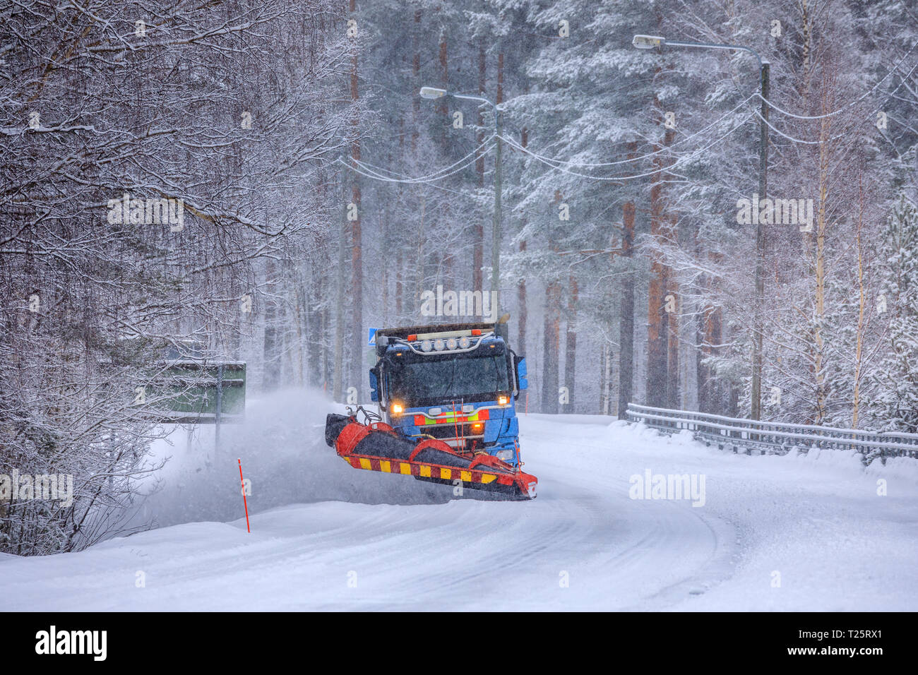 Snowplow removing snow from a snow-covered icy road - Stock Image