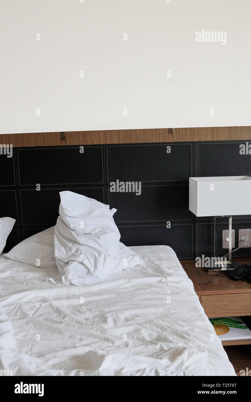 Hotel bedroom with messy double bed - Stock Image