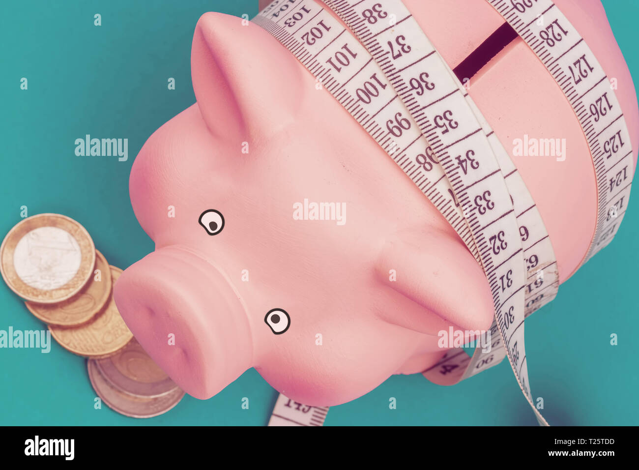 Investments and metering or counting idea. Ceramic toy pig with white flexible ruler on blue background. - Stock Image