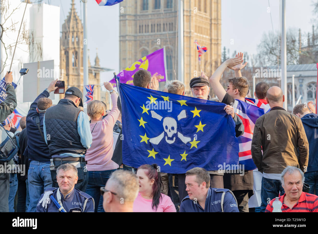 Westminster, London, UK; 29th March 2019; Pro-Brexit Demonstrator Holds Flag During the March to Leave Rally in Parliament Square. Parliament Behind - Stock Image