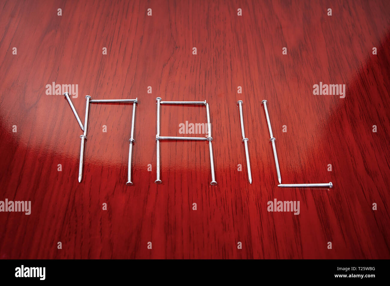 An organized group of nails forming the word nail - Stock Image