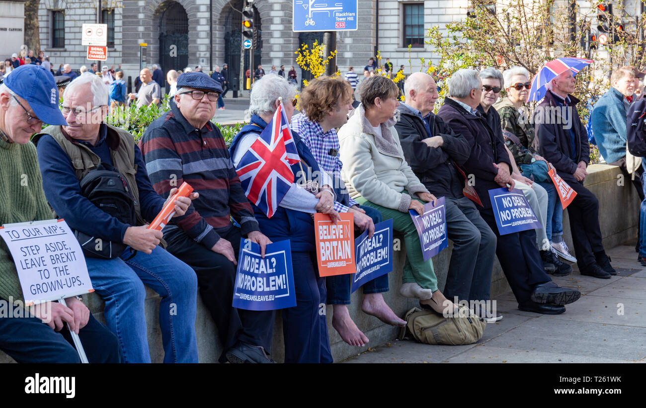 Westminster, London, UK; 29th March 2019; Row of Pro-Brexit Demonstrators Sit on a Wall During the March to Leave Rally. Most Hold pro-Brexit Signs - Stock Image