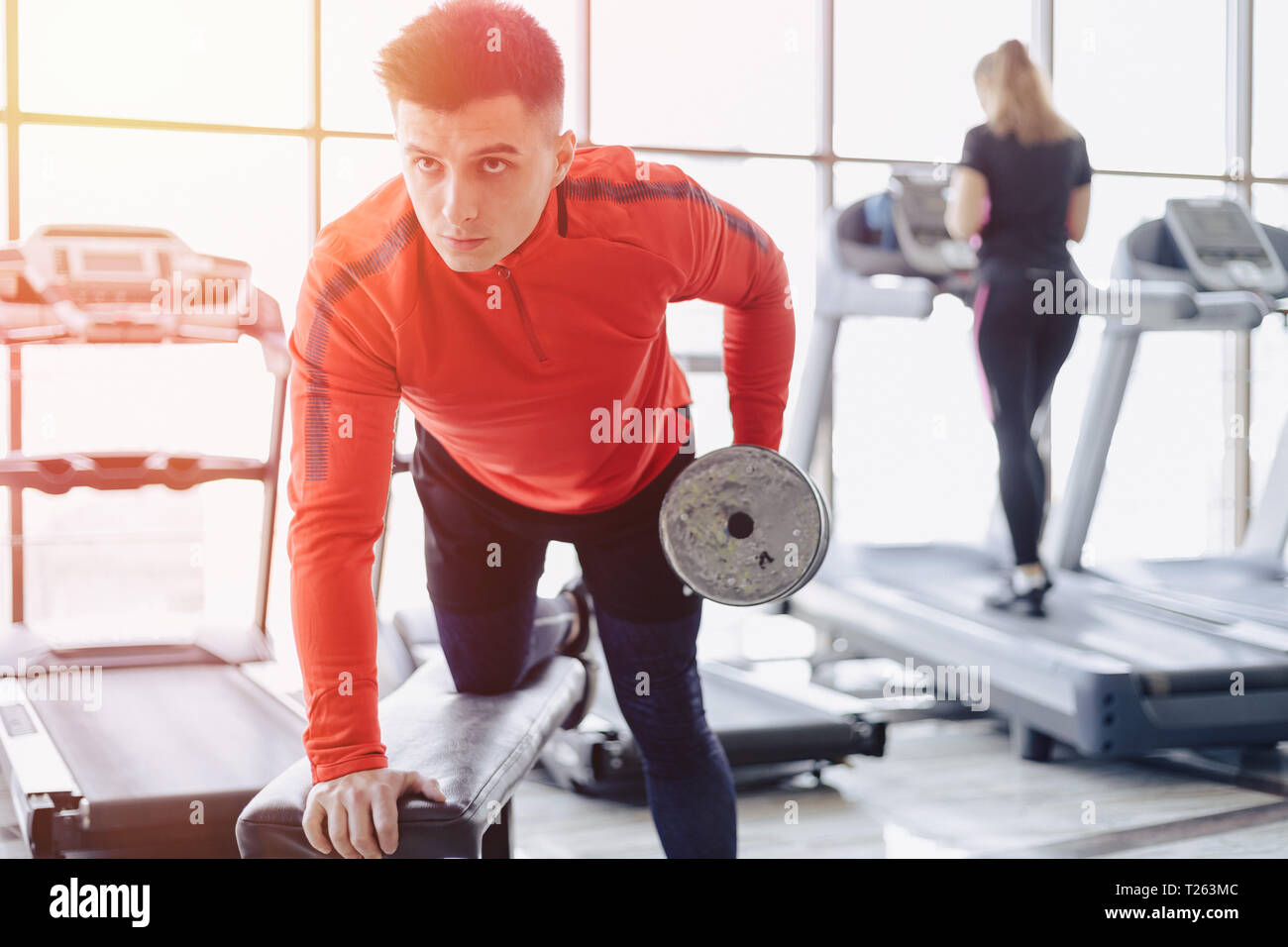 A man dumps triceps on the background of treadmills at the gym - Stock Image