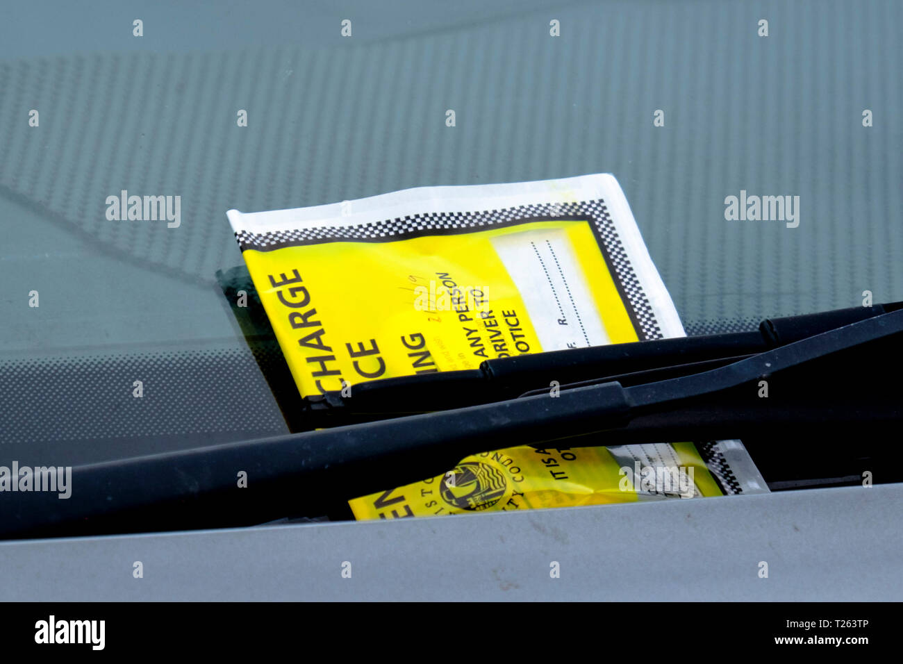Fixed charge parking notice on a windscreen under a winds screen wiper - Stock Image