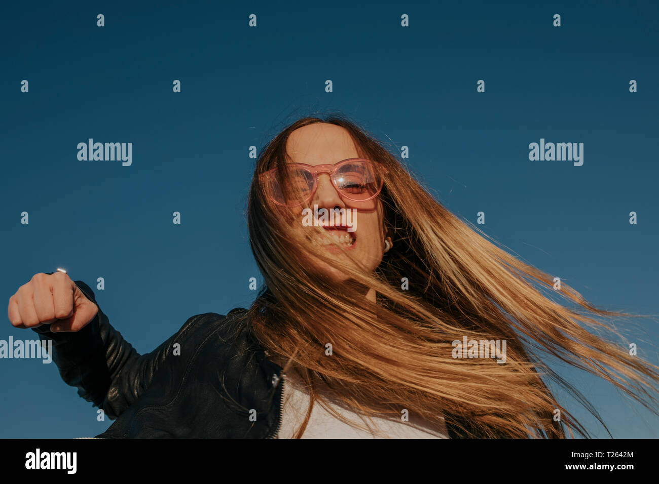 Portrait of aggressive young woman punching under blue sky - Stock Image