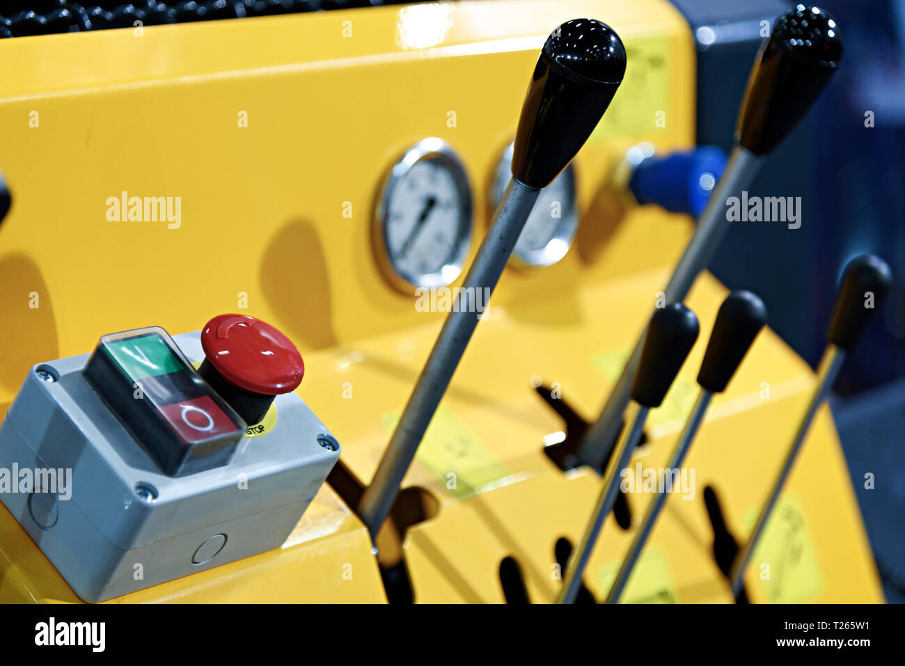 Close-up of a yellow control panel and security red stop button in the industrial machine . - Stock Image