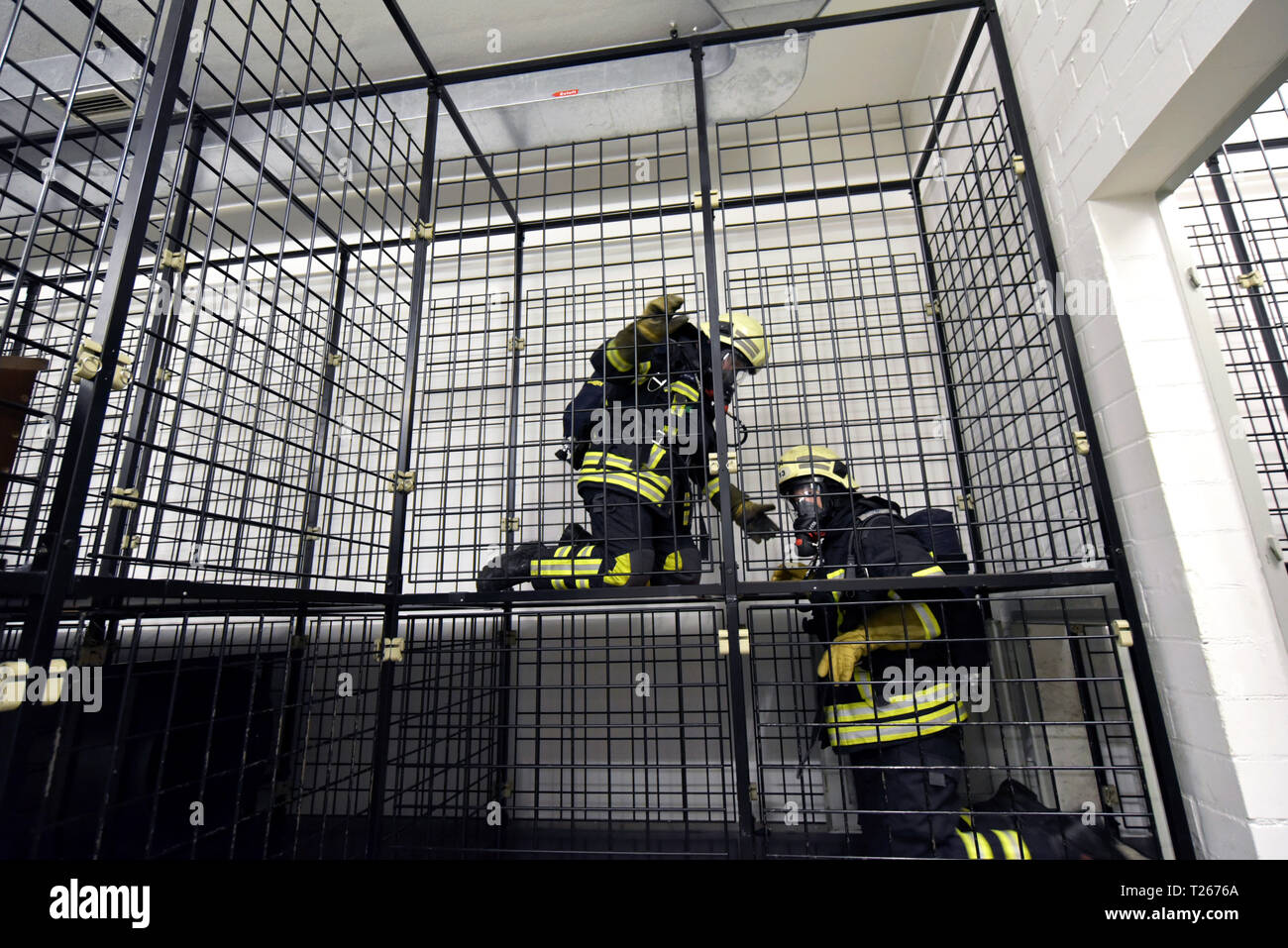 Two firefighters with respirator and air tank exercising - Stock Image