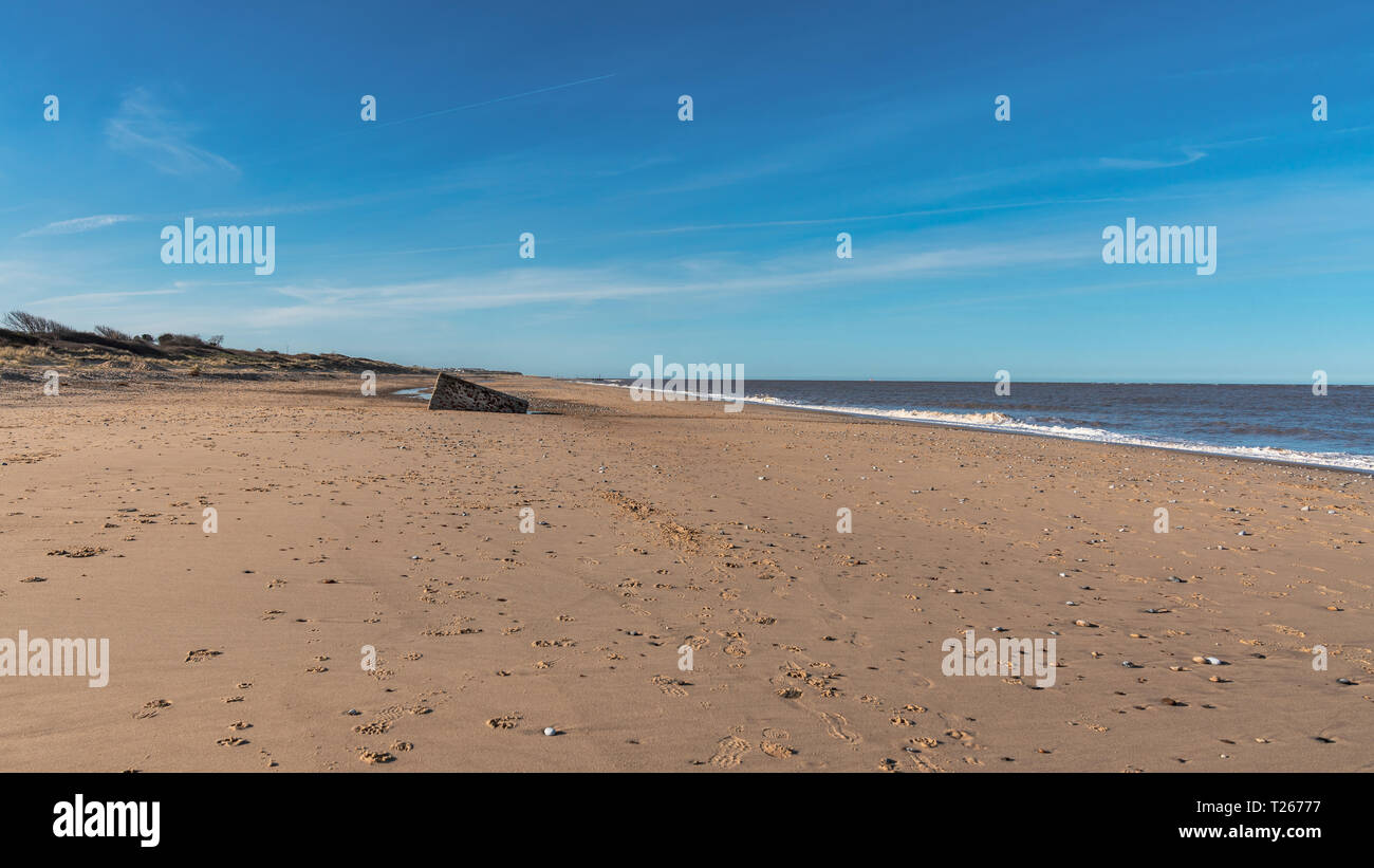 North sea coast in Caister-on-Sea, Norfolk, England, UK - with an old bunker on the beach Stock Photo