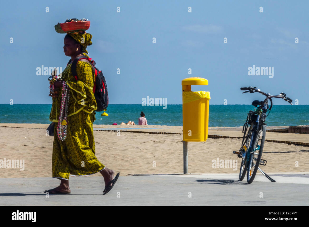 African woman in traditional clothes selling small jewelry on the beach, Valencia Malvarrosa Spain - Stock Image