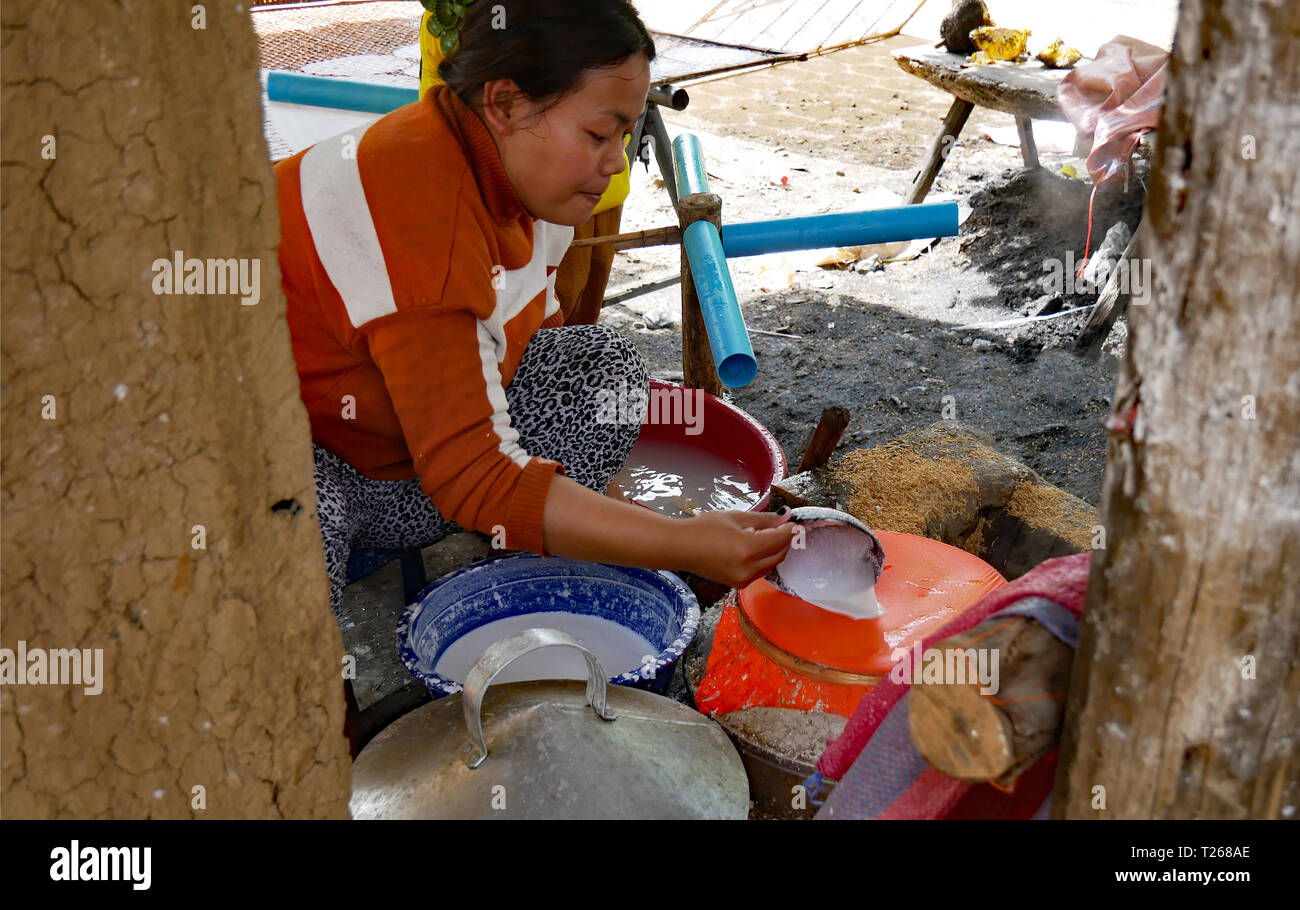 Battambang, Cambodia, Spreading rice paste the onto the surface of the home made steam cooker when making rice-paper for spring rolls 10-12-2018 - Stock Image