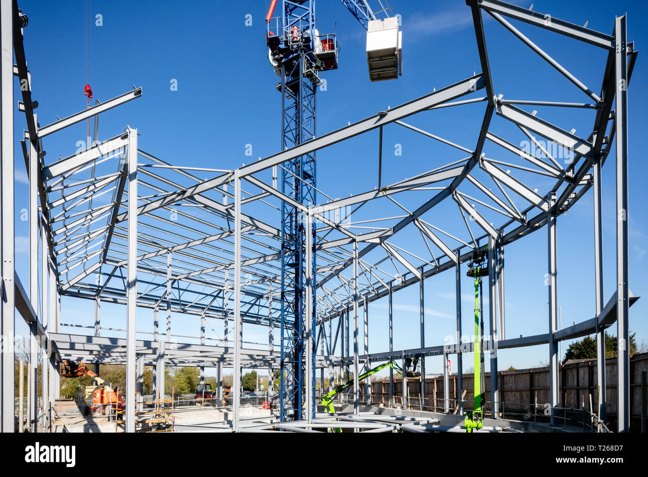 Steel frame of new building in construction set against bright blue sky. Building site. Construction site - Stock Image