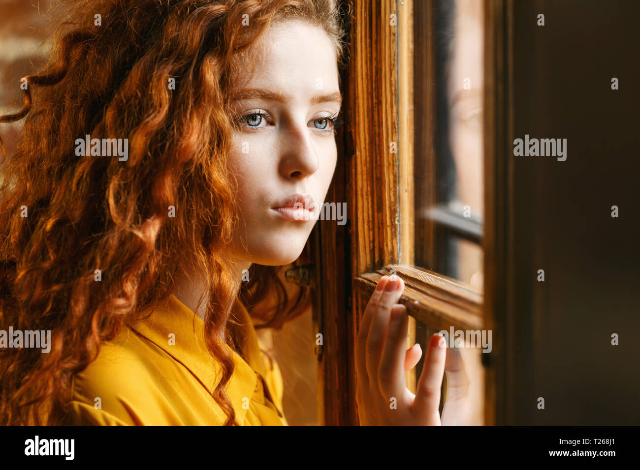 663fc6ffb33 Pensive curly ginger girl in the yellow shirt looking to the window at the  loft interior