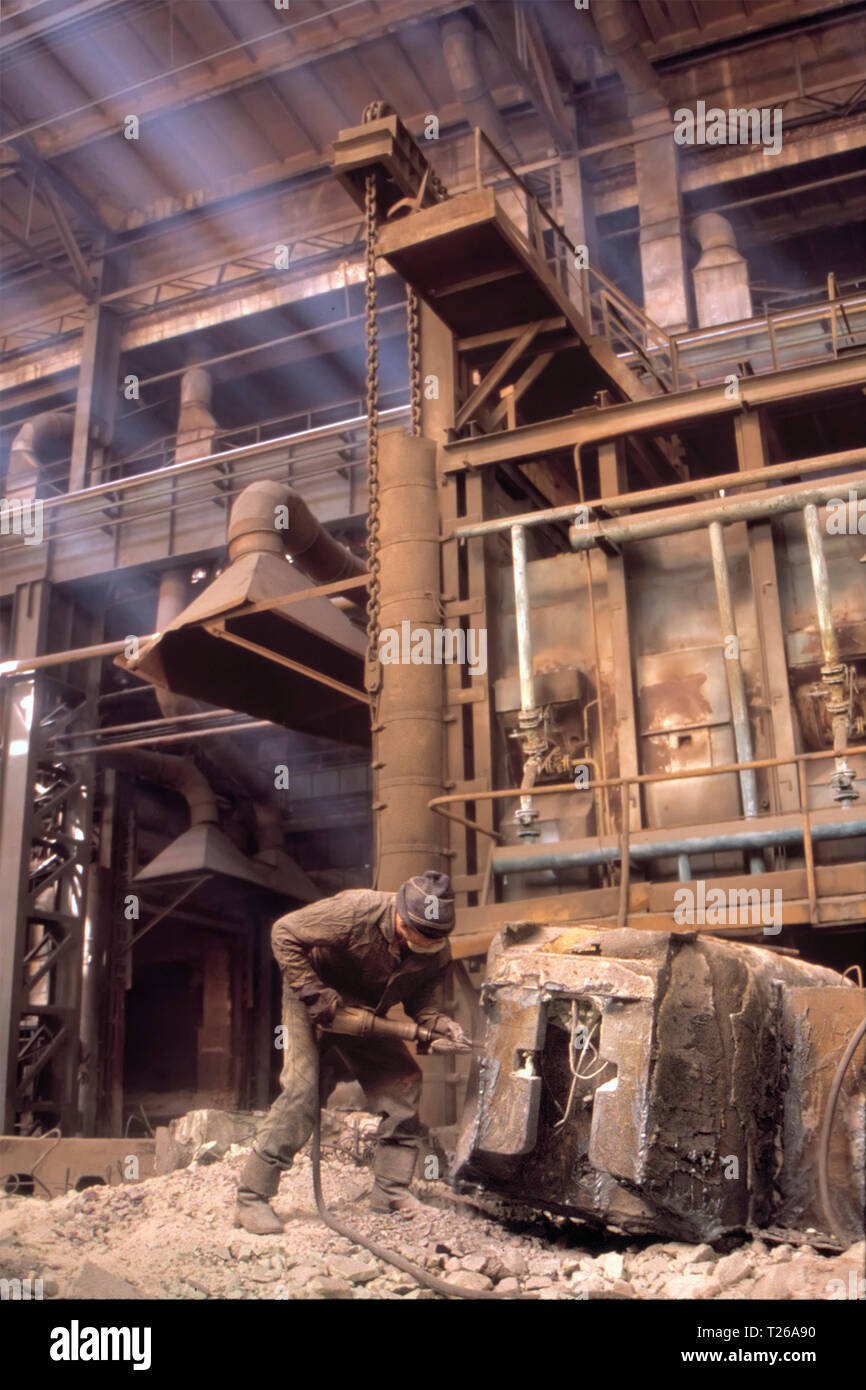 Hardest work in world. Difficult working conditions. High risk of injuries in workplace. Unprotected worker doing hard and dirty work at metallurgical - Stock Image