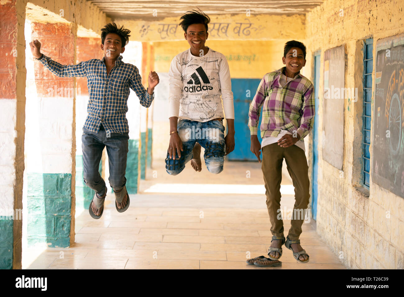 Young Bhil tribe boys acting silly, fooling around outside their village school in Rajasthan, India. Stock Photo