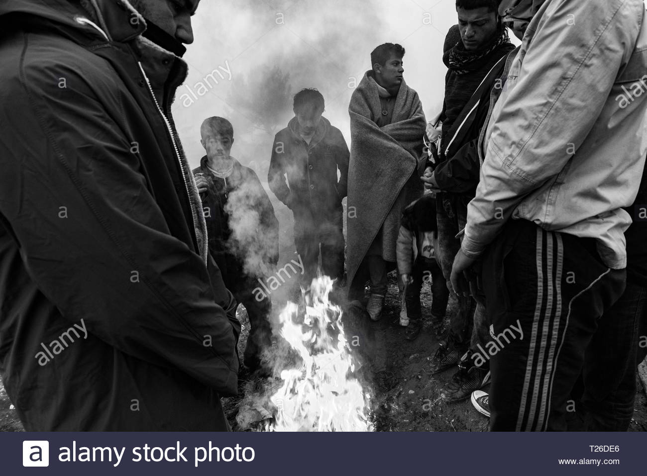 In the evening temperature are below zero, therefore refugees warming themselves by lighting fires at Greek-Macedonian border.  Idomeni, Greece, 8 March 2016.The refugee camp to which thousands of immigrants, mainly Syrians, are coming. It is occupied by people from different social strata. They are all found there fleeing the war, death and starvation. They continue their journey through Macedonia to the north and west of Europe. Not everyone manages to pass the verification of the documents, which leads to the separation of families. The refugees are living in difficult conditions. - Stock Image