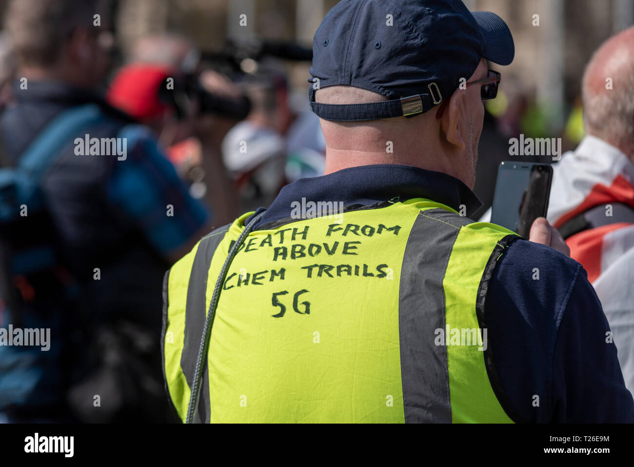 Male yellow vest wearer at Brexit with hand written slogan death from above chem trails 5G. Conspiracy theory. Conspiracy theories. Using mobile phone - Stock Image