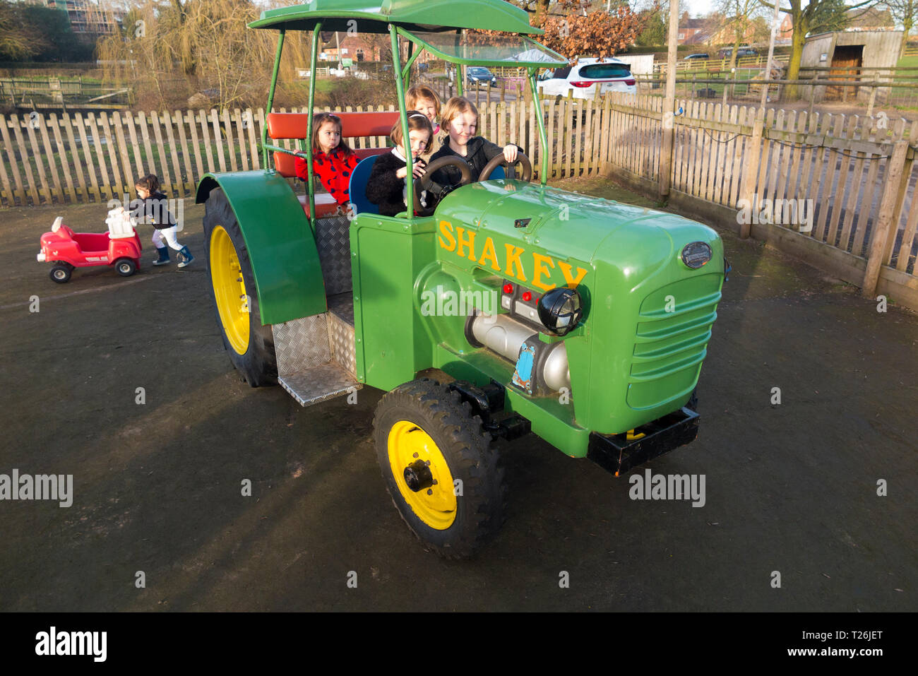 Kids / children / child on a life size model toy tractor of large scale size at a farm shop in Congleton, Cheshire England UK (106) - Stock Image