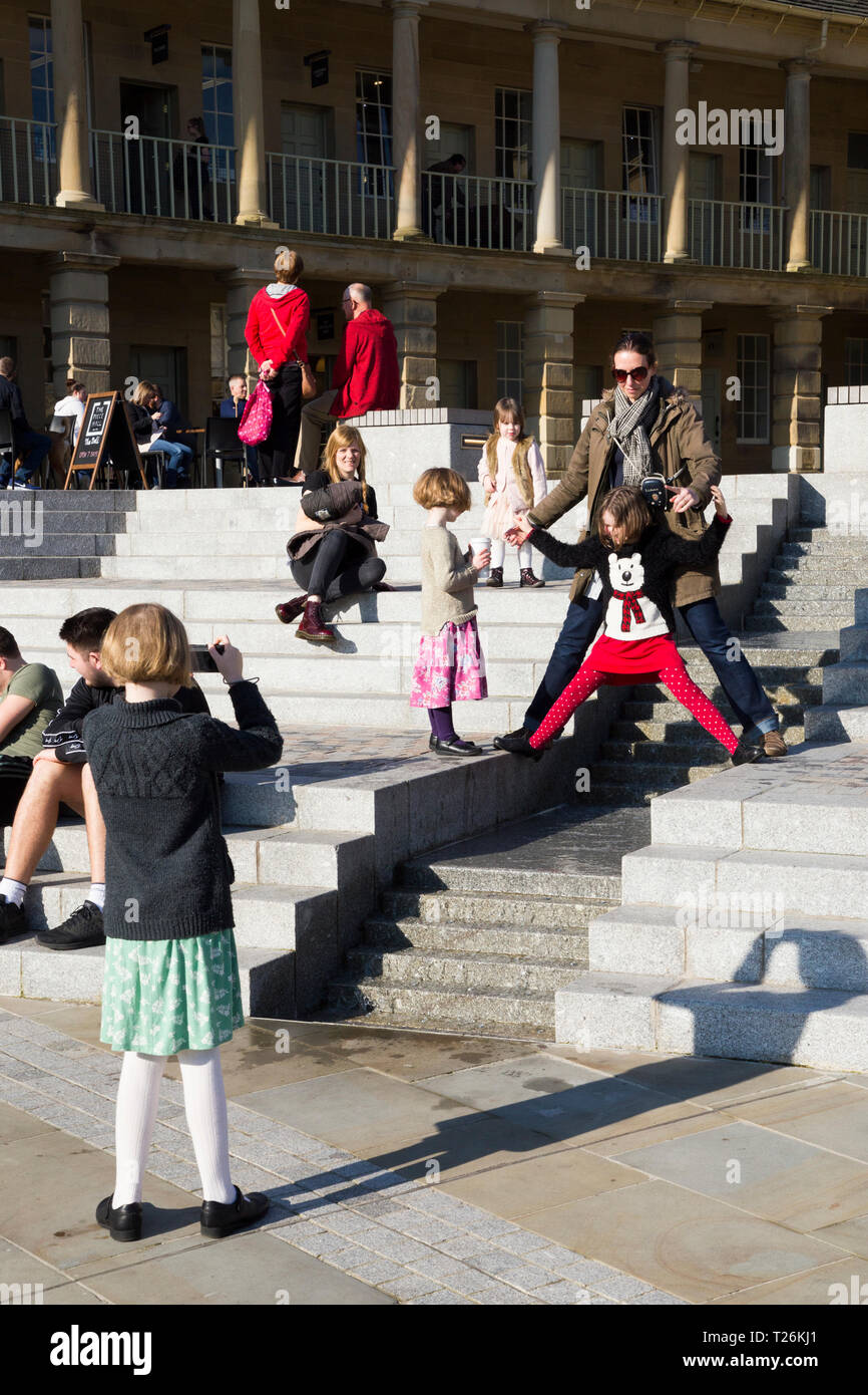 Child plays around the water feature & visitors / tourists sit & relax on the steps inside the quadrangle of the restored Piece Hall. Sunny day / sun. Halifax. England UK. The day was an unusually hot day during winter. - Stock Image