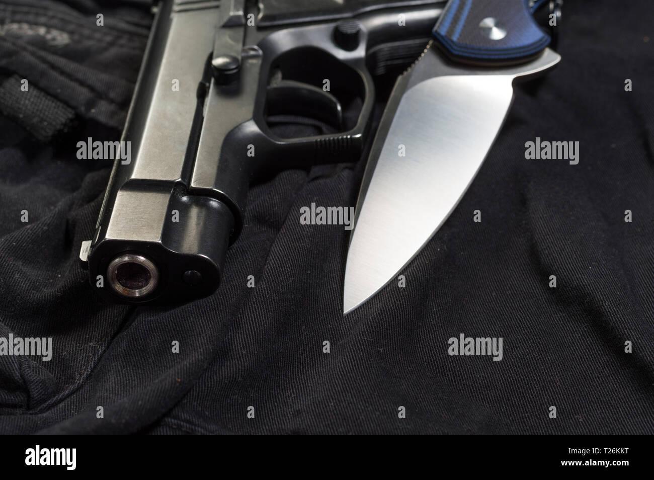 Muzzle pistol and knife blade. Weapon close-up. Front view. - Stock Image
