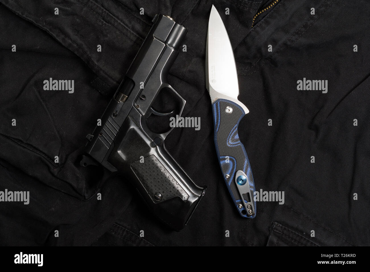 Firearm and knife. Weapons and men's clothing. Top. - Stock Image