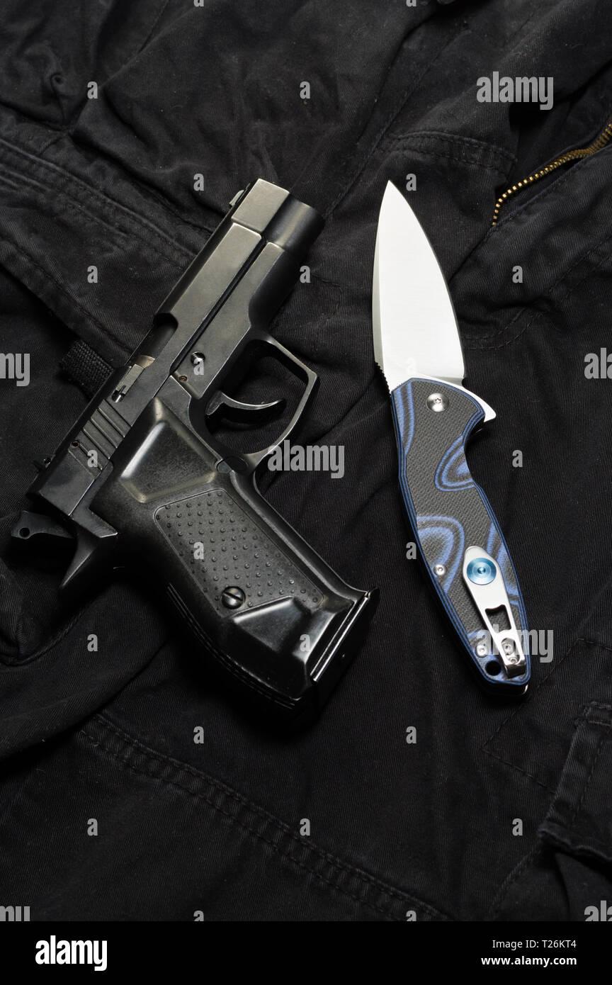 Pocket knife and pistol. Weapons on a black background. Vertical frame. - Stock Image