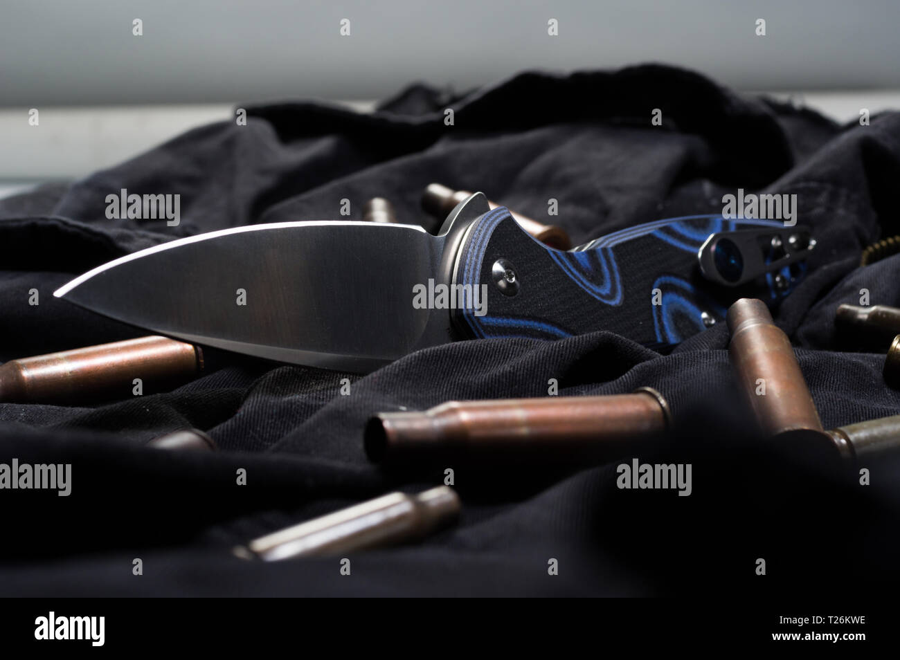 Scattered ammunition on a black background. Cartridges and knife. Front view. - Stock Image