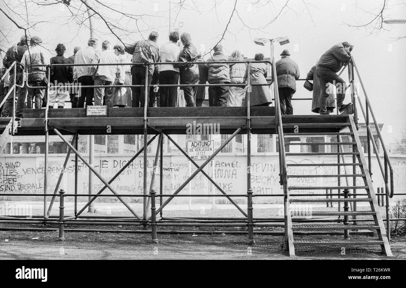 West Germany, West-Berlin, the wall in year 1988, visitors on observation platform at Brandenburg Gate on the West Berlin side viewing East Berlin side in GDR , scan from 35 mm black and white negative - Stock Image
